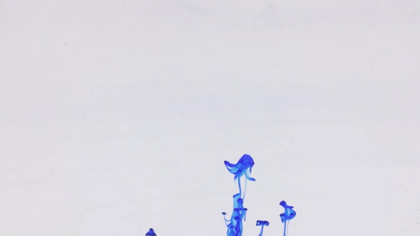 Chaotic movement of drops of blue paint in water. Ink in water. Close-up. Stok Video