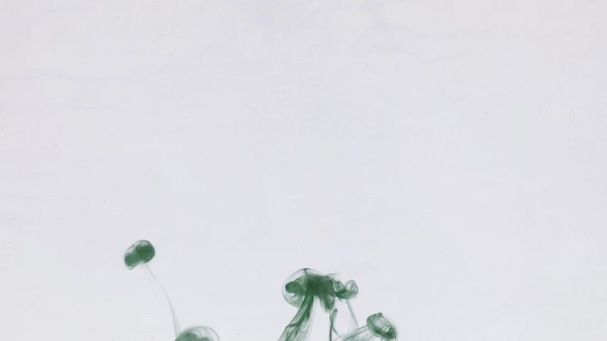 Chaotic movement of drops of green paint in water. Ink in water. Close-up.