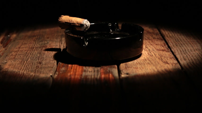 Cigar is lying in an ashtray on a wooden table. Illuminated by the spotlight.