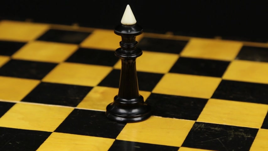 Rotation. Chess figure black king on chess board. Close-up