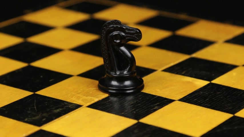 Rotation. Chess figure black horse on chess board. Close-up
