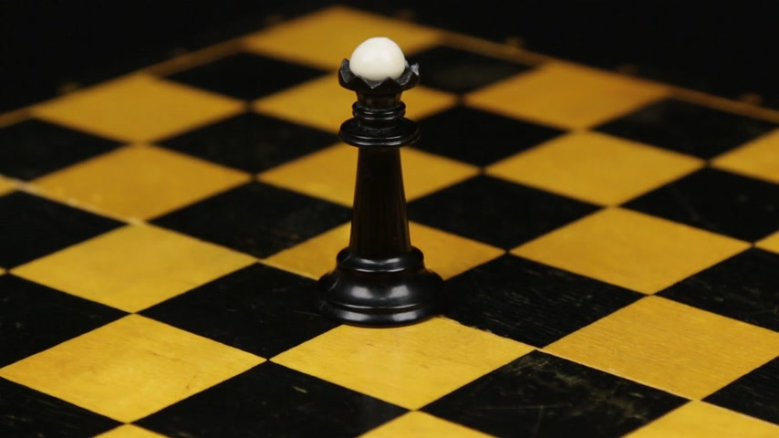 Rotation. Chess figure black queen on chess board. Close-up