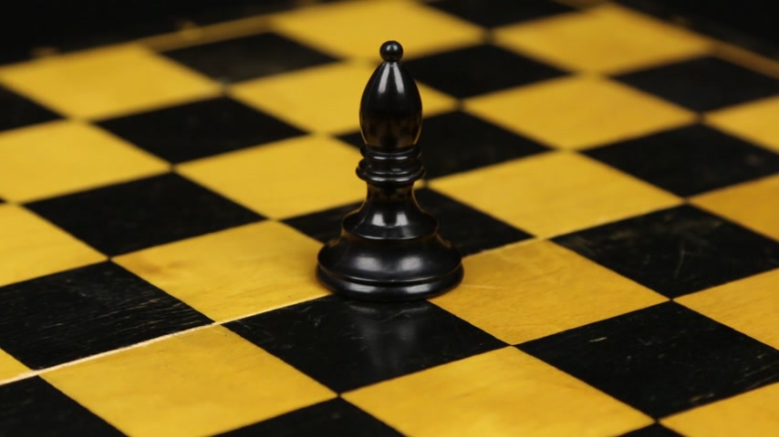 Rotation. Chess figure black bishop on chess board. Close-up