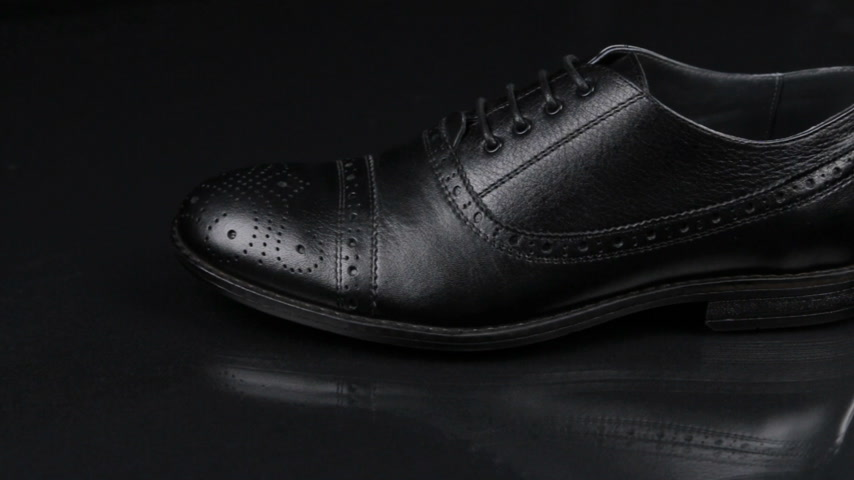 Elegant male shoes with laces stand on a black background with a beautiful reflection. Slider shot.