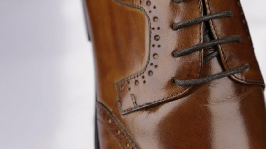 new clothes : Mens shoes, close-up of brown shoelaces. Rotation. Stock Footage