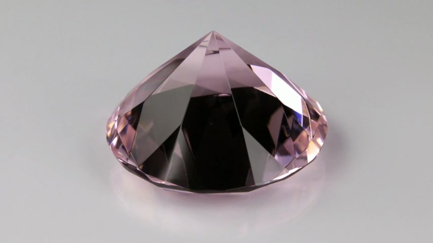 klenot : Rotation of a pink transparent rhinestone on a white background.