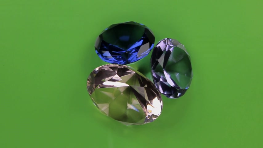 kuvars : Rotation of a three transparent rhinestone on a green screen. Stok Video