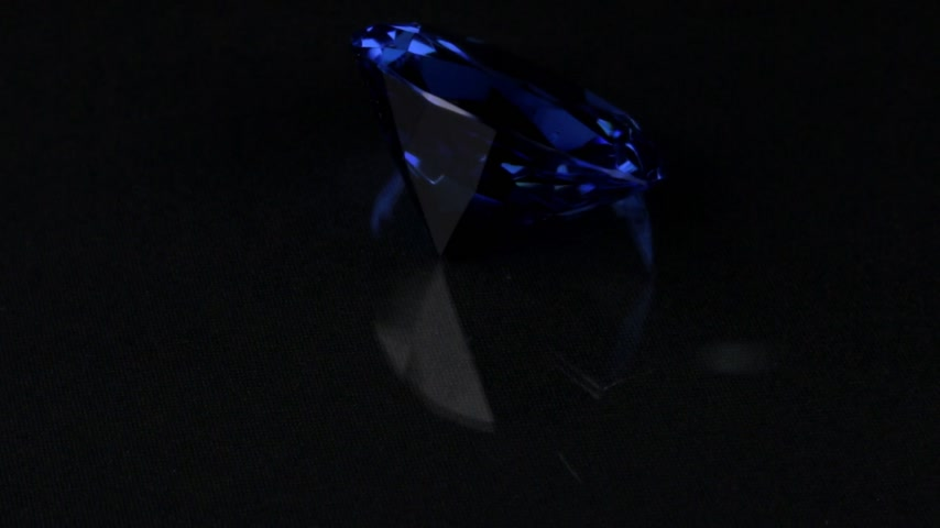 Rotation of a blue transparent rhinestone on a black background. Stok Video