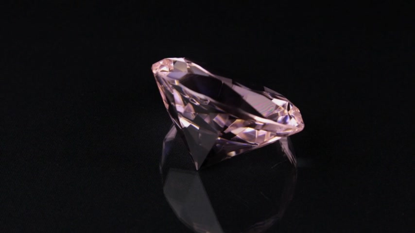 Rotation of a pink transparent rhinestone on a black background.