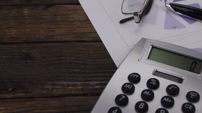 Office desk with charts, glasses, pen and calculator. Slider shot. Business and finance