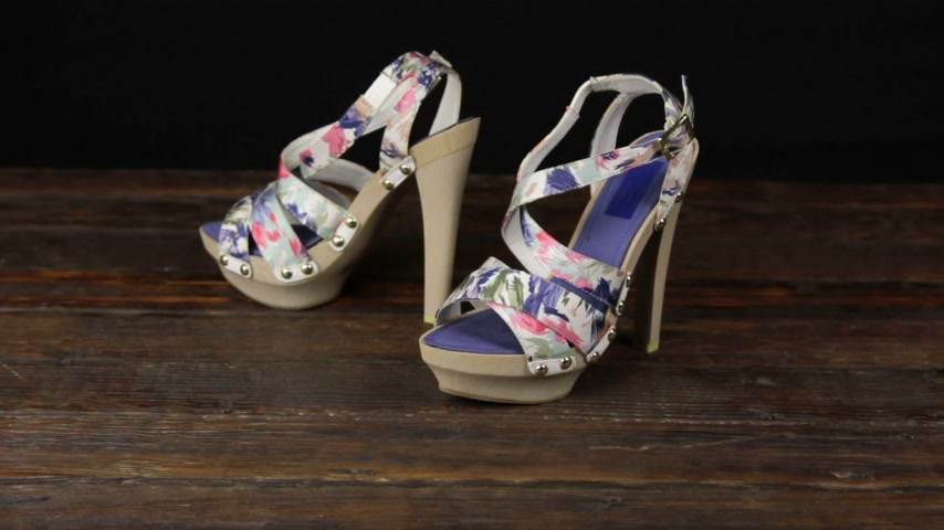szandál : Beige sandals with high heels and a platform on a wooden background.