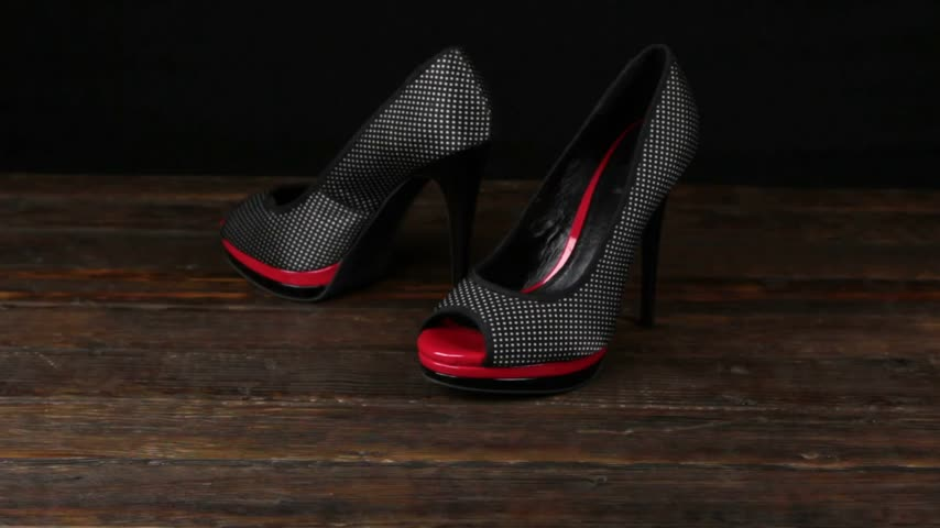 szandál : Black shoes with high heels and a platform on a wooden background.