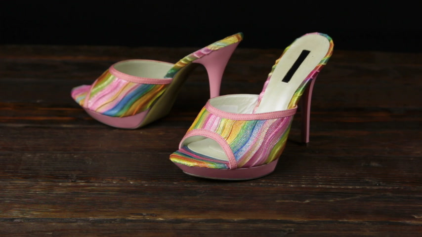 dois objetos : Pink clogs with high heels and a platform on a wooden background.