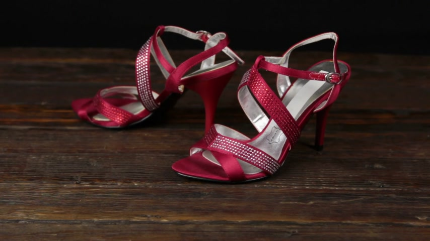 Red sandals with high heels on a wooden background.