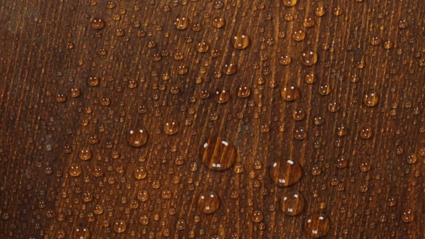 Rotation of a drop of water on a beautiful wooden surface.