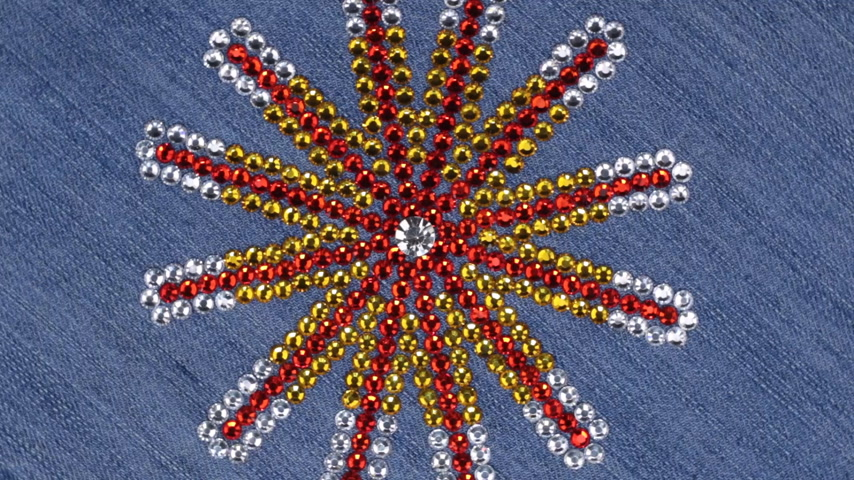 Rotation of multi-colored rhinestones laid out in the shape of a star on denim. Stock mozgókép
