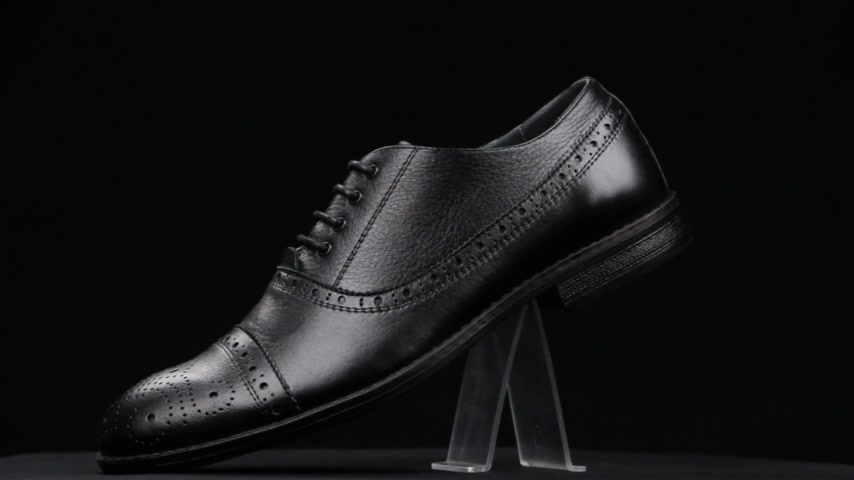Rotation and approximation of black classic mens shoes on a black background. Copy space.