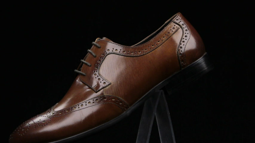 Rotation and approximation of brown classic mens shoes on a black background. Copy space. Stok Video