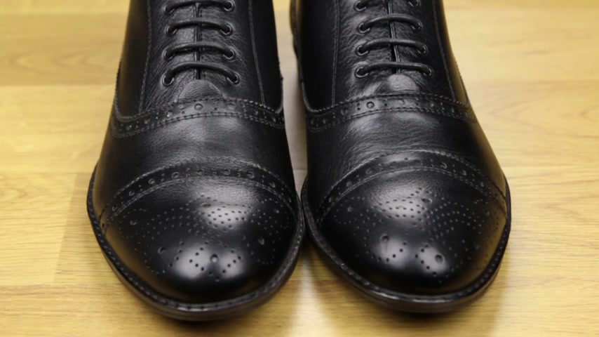 cipőfűző : Approaching, pair of black classic mens shoes standing on a wooden floor. Mens fashion. Stock mozgókép