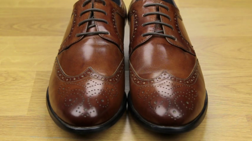 Approaching, pair of brown classic mens shoes standing on a wooden floor. Mens fashion.