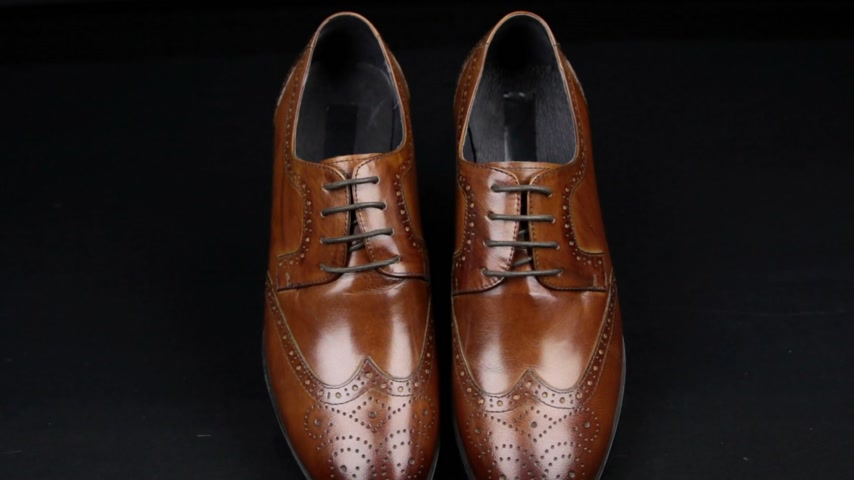 Approaching, pair of brown classic mens shoes standing on on a black background. Mens fashion
