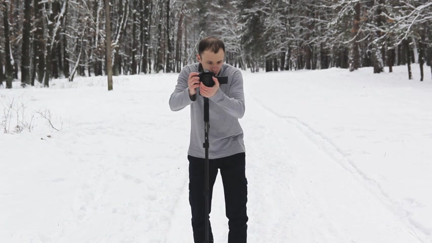 film camera : a guy in a snow-covered forest shoots a video