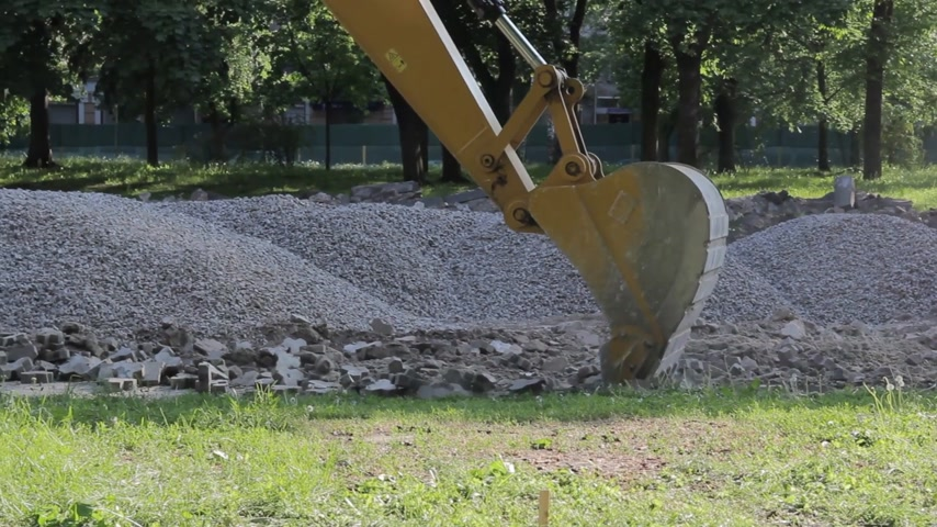 backhoe loader : Excavator bucket digging a trench at the side of the road for its expansion