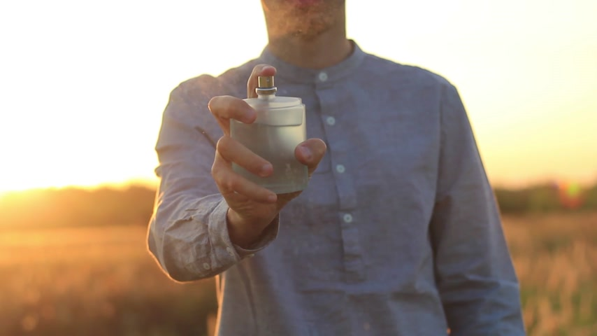 dezodorant : hands of a young man using perfume at sunset Wideo