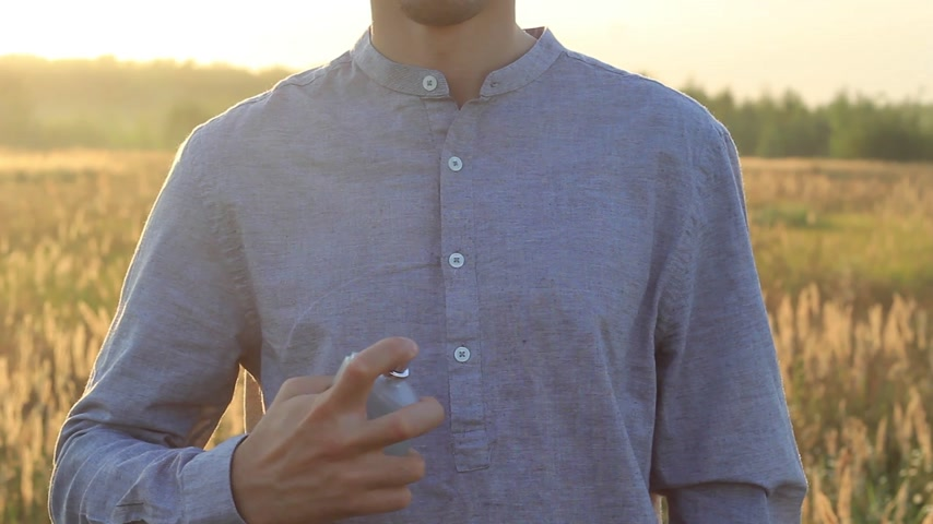 perfume bottle : hands of a young man using perfume at sunset Stock Footage