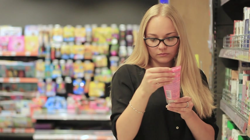 beauty products : girl in the supermarket chooses cream