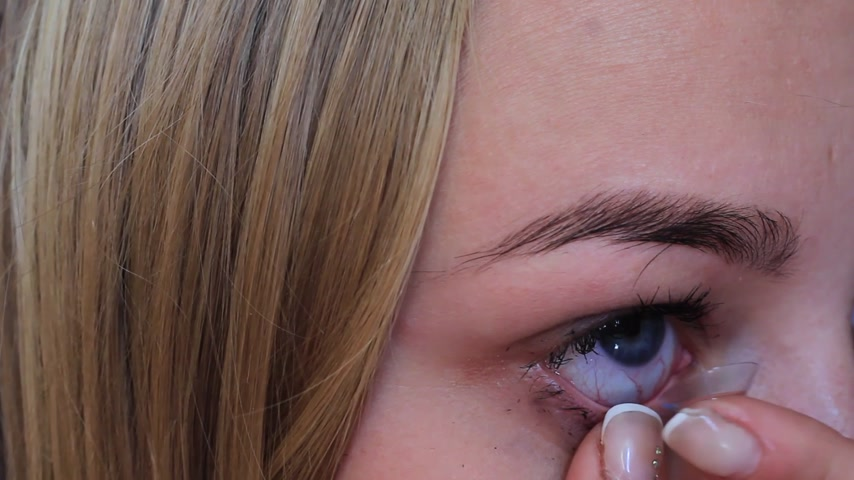 kontakt : girl inserts an optical lens into the eye