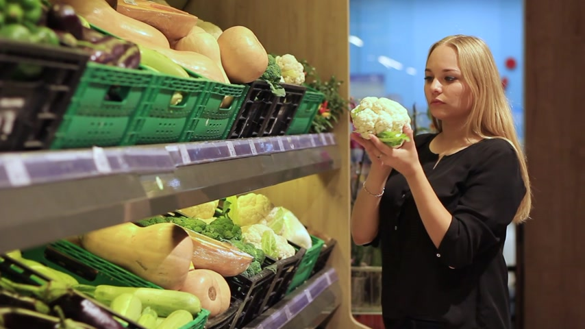shopping cart : girl chooses vegetables and fruits in the supermarket