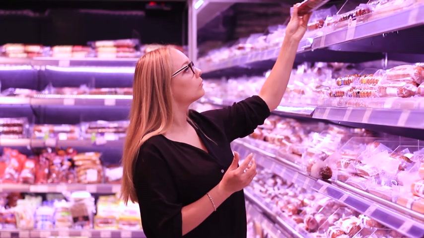 butchers shop : The girl in the meat department chooses sausage