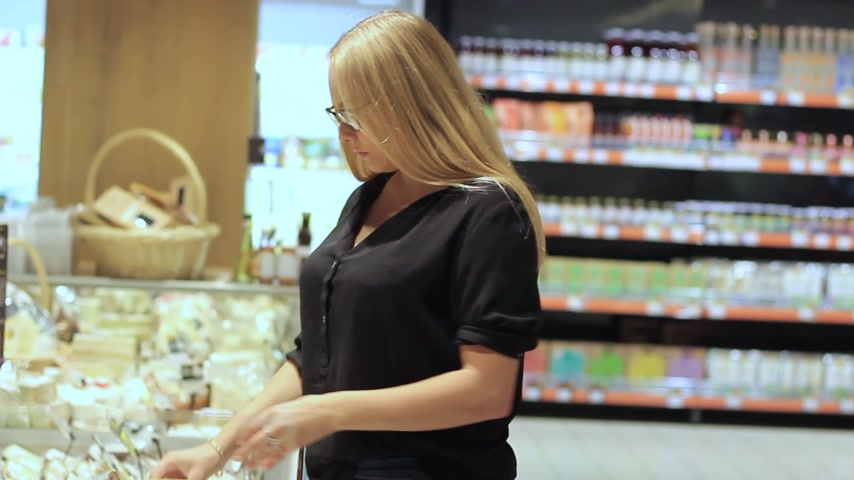 cheddar : girl in a supermarket chooses cheese Stock Footage