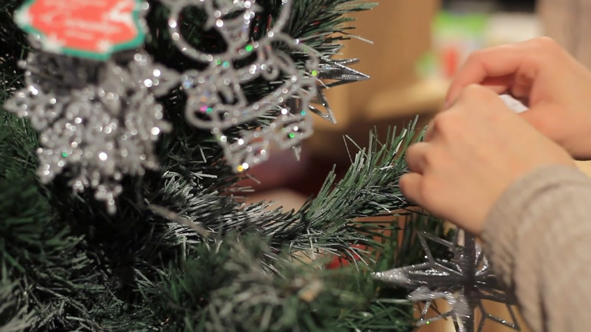 plywood : New Year. Female hand puts toys on the Christmas tree.