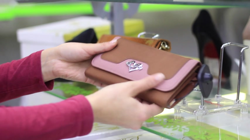 handbag : female hands chooses a female handbag in the store