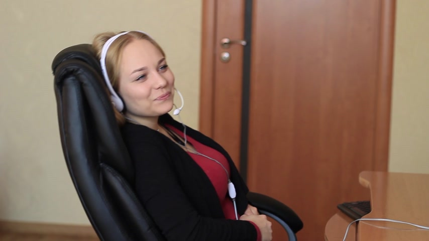телемаркетинг : The girl in the headset is sitting on a chair near the computer Стоковые видеозаписи