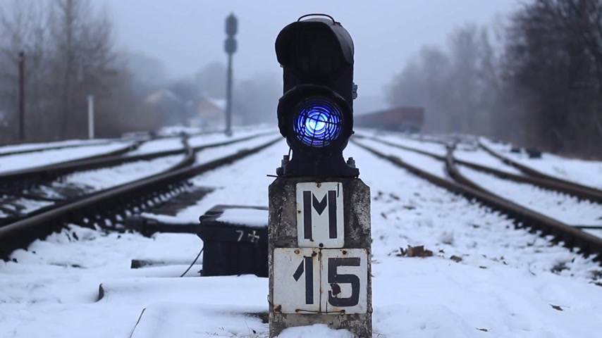 Semaphore on the railway in winter, glowing blue. Gloomy scene Stock Footage
