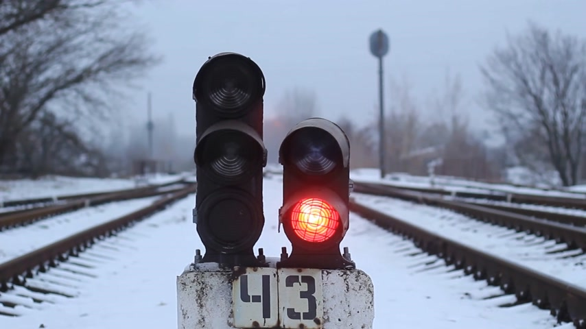 Semaphore on the railway in winter, glowing red. Gloomy scene