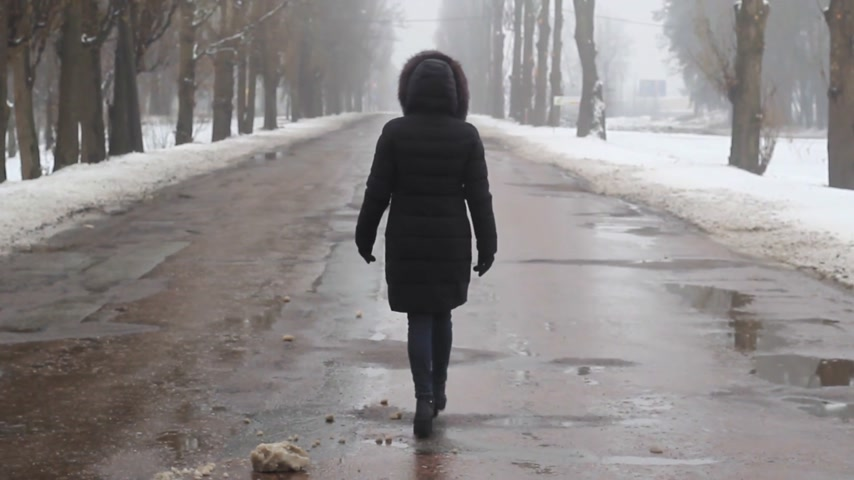 girl goes on a foggy broken road in the winter Stock Footage