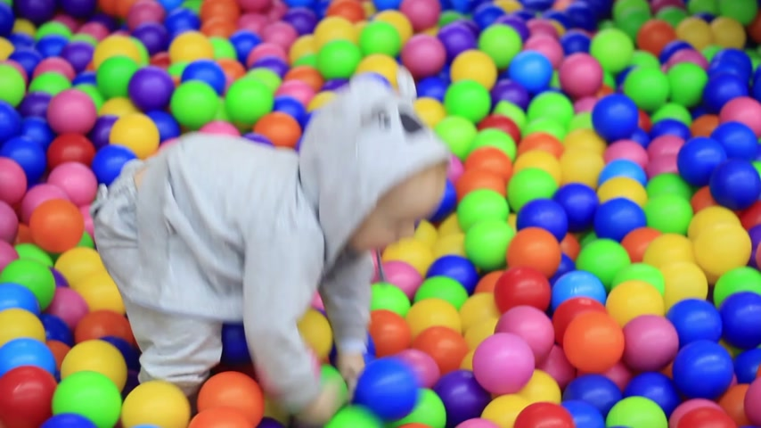 little boy having fun on the playground with colored balls