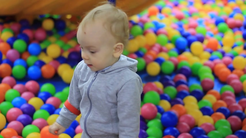 little boy on the playground with colored balls around