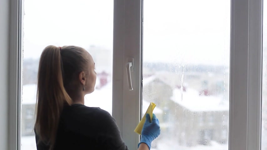 girl washes a window in the apartment Stock Footage