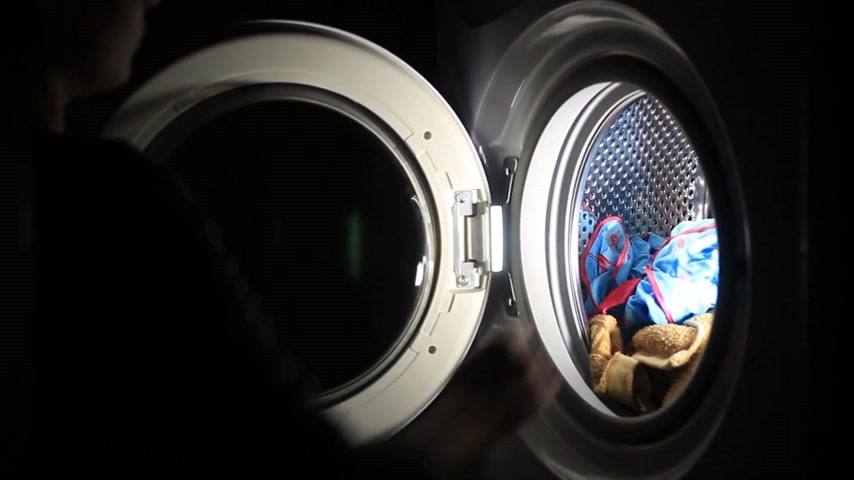 lavanderia : Female hands down dirty clothes to washing machine Stock Footage