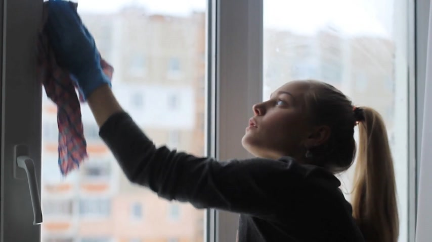 girl washes a window in the apartment.
