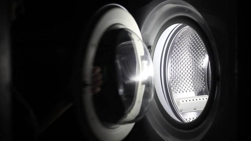 Female hands down dirty clothes to washing machine Stock Footage