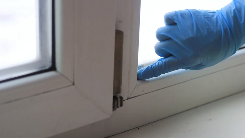 уборка : Female hand in a rubber glove close up removes the window frame