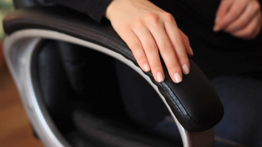 The female hand is on the handle of a computer chair close up