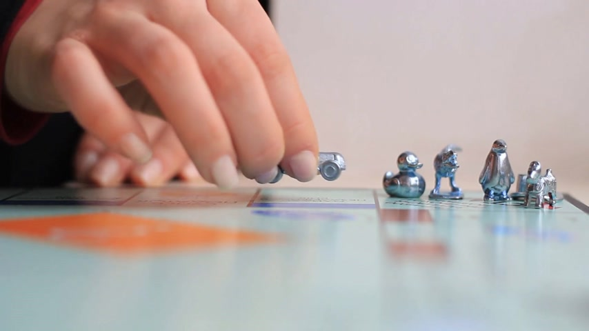 The game of monopoly close-up. Female hand makes moves in the game