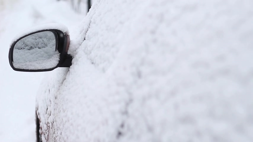 Snow covered side view mirror of a modern car Stock Footage